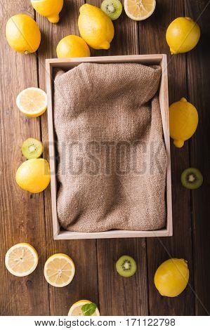 Lemons and kiwi on a wooden background. Lemons. Fruits. Lemon halves. Mint. Healthy food concept. Copyspace. Wooden box with burlap