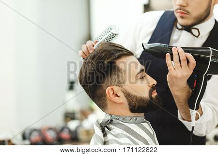 Man wearing white shirt doing a haircut with hair dryer and hair brush for man with black hair at barber shop, copy space, portrait.