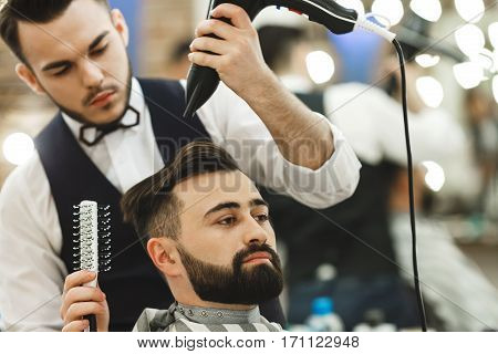Handsome man wearing white shirt doing a haircut with hair dryer and hair brush for man with black hair at barber shop, mirror at background, portrait, copy space.