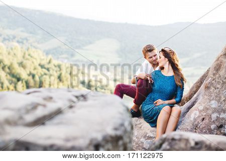 Nice couple sitting on high rock, outdoor. Girl leaning on her boyfriend's knee. Man holding girl's hand. Beloved looking at each other. Woman wearing blue dress and man wearing white shirt, black shoes and claret trousers