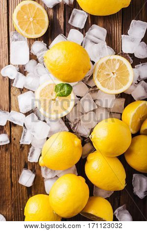 Lemons and ice on a wooden background. Lemons. Fruits. Kiwi. Mint. Healthy food concept. Copyspace