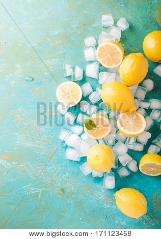 Lemons and ice on a turquoise background. Lemons. Fruits. Mint. Healthy food concept. Copyspace