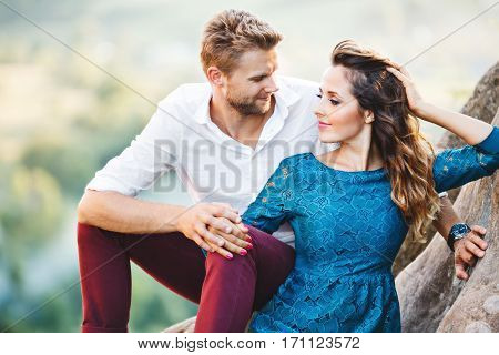 Cute couple sitting on rock, outdoor. Girl leaning on her boyfriend's knee and holding her hand on her hair. Man looking at girl and holding her hand. Woman looking aside. Woman wearing blue dress and man wearing white shirt and claret trousers. Waist up,