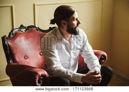 Handsome man sitting on red chair. Bridegroom looking aside. Fingers crossed. Man in white shirt with beard and moustache. Profile. Indoor, studio