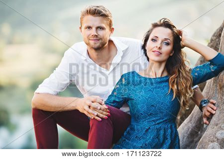 Cute couple sitting on rock, outdoor. Girl leaning on her boyfriend's knee and holding her hand on her hair. Man holding her hand. Beloved looking at camera. Woman wearing blue dress and man wearing white shirt and claret trousers. Waist up, closeup