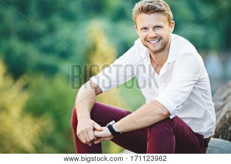 Handsome man sitting on rock, outdoor. Boy leaning on his knees and holding his hands together. Man wearing white shirt, claret trousers and watch. Looking at camera and smiling. Waist up, closeup
