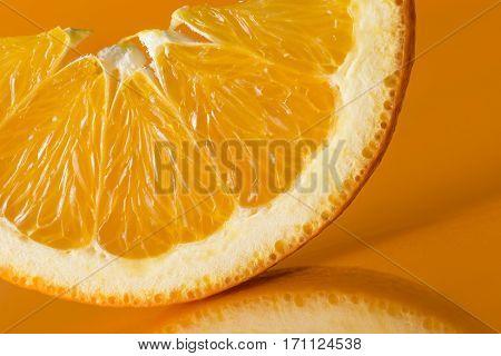 Studio shot of slice of orange fruit isolated on orange background. Selective focus