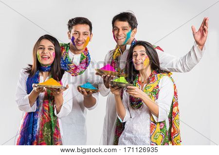 4 indian friends or 2 young couples celebrating Holi festival with sweets, bhang, pichkari and hands painted with gulal having copy space, isolated over white background