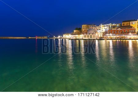 Picturesque view of Venetian quay of Chania with Kucuk Hasan Pasha Mosque during twilight blue hour, Crete, Greece