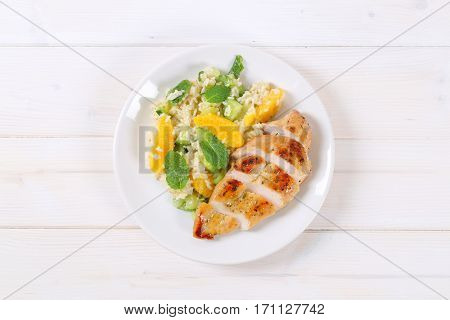 roasted chicken with rice and oranges on white plate