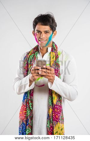 Technology and festival concept - Handsome indian man using smartphone or cel phone on Holi, isolated over white background