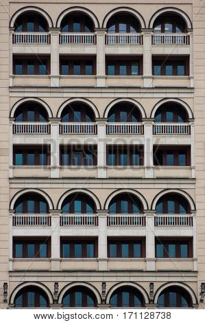 Building's facade. Many windows. Balconies and arches