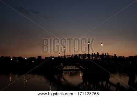 Bridge in the park at sunset. People on a walk