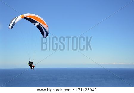 Extreme sport paragliding over the ocean through clear blue sky. Copy space for text. Stanwell Tops, New South Wales, Australia