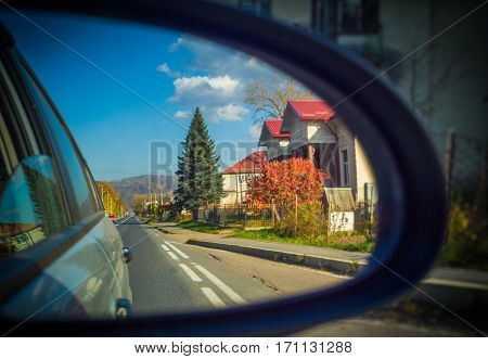 Rearview mirror. Road and house in reflection.