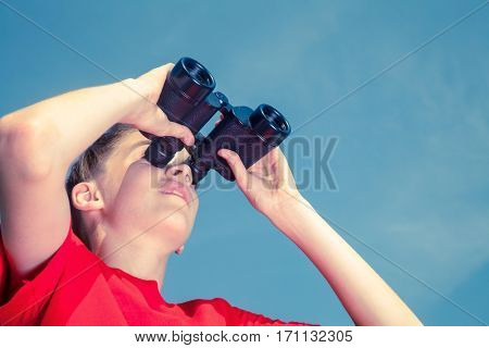 Low angle view of birdwatcher teen boy wearing red tshirt looking through binoculars at birds against blue summer sky