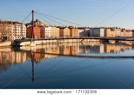 Lyon citycsape with red suspension footbridge over the Saone river and waterfront buildings in the evening light France Central Europe