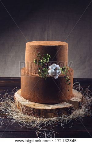Truffle Chocolate Tiered Cake Dusted With Cocoa On Wooden Stand