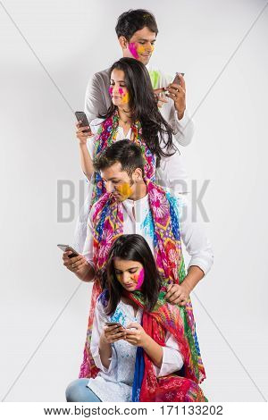 2 indian young couples or 4 indian people using mobile phone on the occasion of Holi - Festival of colours, with faces painted in traditional indian ethnic wear, standing over white background