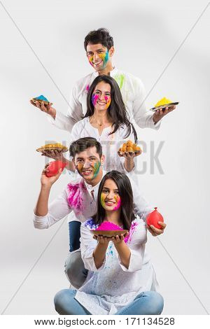4 indian friends or 2 young couples celebrating Holi festival with sweets, bhang, pichkari and hands painted with gulal having copy space, isolated over white background standing in one line