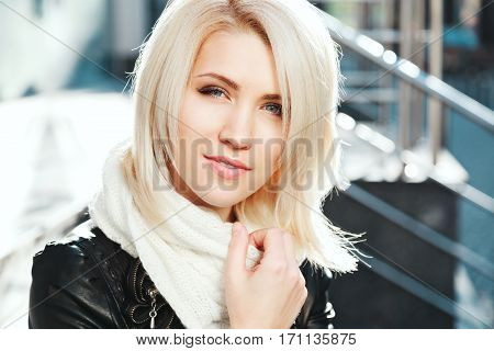 Gorgeous blonde girl with nude make up wearing black jacket and white scarf, portrait, city behind.