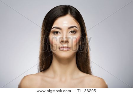Model with professional contour and highlight makeup. Contouring face make-up applying sample. Beauty portrait, head and shoulders, full face. Indoor, studio