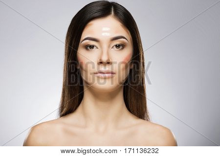 Girl with professional contour and highlight makeup. Contouring face make-up applying sample. Beauty portrait, head and shoulders, full face. Indoor, studio