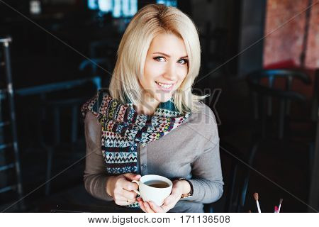 Beautiful blonde girl with nude make up wearing gray blouse and scarf, sitting in cafe with cup of coffee, copy space, portrait.