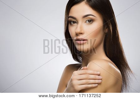 Beautiful girl with nice make-up looking at camera and holding her hand near shoulder. Turned a little bit aside. Beauty portrait, head and shoulders. Indoor, studio, gray background