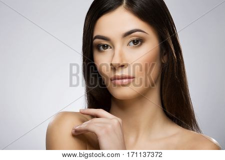 Beautiful girl with nice make-up looking at camera and touching her shoulder by hand. Beauty portrait, head and shoulders. Indoor, studio, gray background