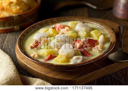 A delicious hot bowl of homemade seafood chowder with lobster haddock clams scallops and saffron.