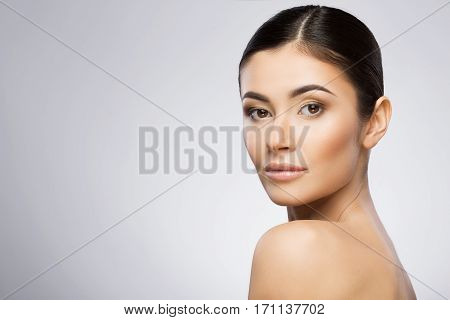 Beautiful girl with nice make-up and ponytail looking at camera. Standing in profile, head turned aside. Beauty portrait, head and shoulders. Indoor, studio, gray background