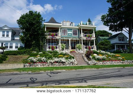 HARBOR SPRINGS, MICHIGAN / UNITED STATES - AUGUST 4, 2016: A mansion with a beautiful flower garden on Bay Street near downtown Harbor Springs.