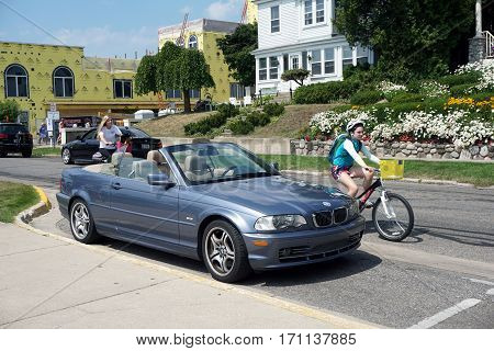 HARBOR SPRINGS, MICHIGAN / UNITED STATES - AUGUST 4, 2016: A blue convertible BMW sports car is parked on Bay Street in downtown Harbor Springs.