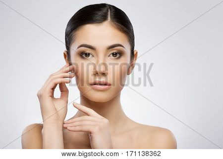 Young model with make-up and ponytail looking at camera. Touching face by one hand. Beauty portrait, head and shoulders, full face. Indoor, studio, gray background