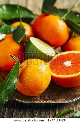 Fresh tangerines with leaves on a plate