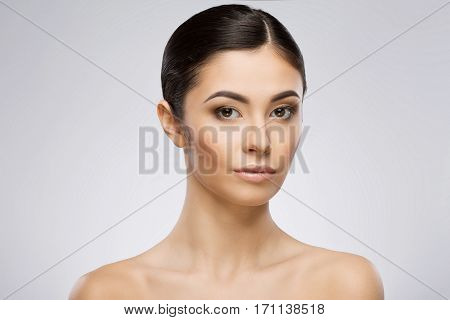 Young woman with make-up and ponytail looking at camera. Head turned a little bit aside. Beauty portrait, head and shoulders. Indoor, studio, gray background