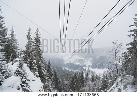 Cableway in the mountains in winter. Perspective view of the mountain woods and rope ropeway.