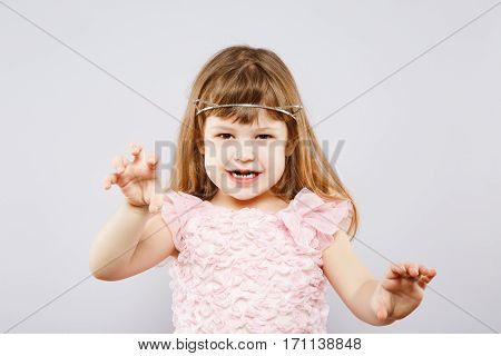 Lovely little girl wearing pink dress and metal cat ears and posing like tiger, looking at camera, gray studio background, copy space, portrait.