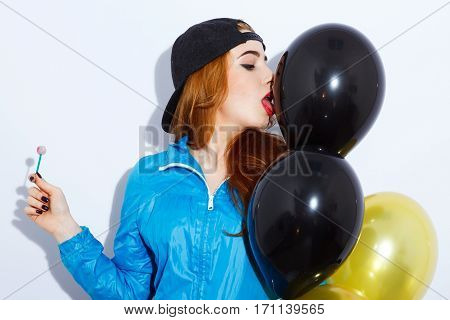 Attractive teenage red-haired girl with long hair wearing blue jacket and black hat holding and licking balloons, holding candy, red lips, black manicure, pathos emotion.