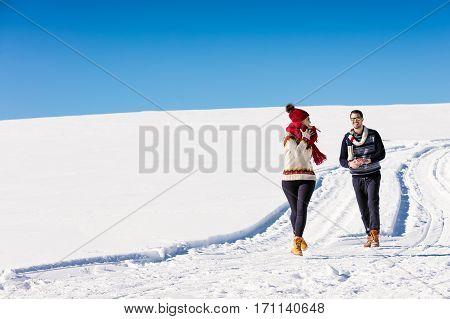 Couple having fun running down slope on winter at mountain.