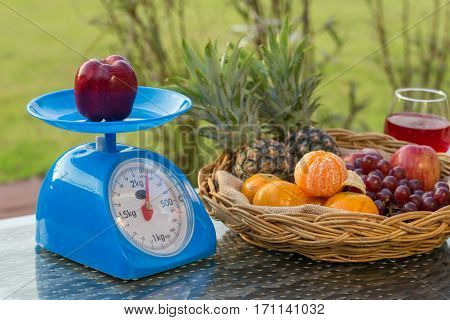 Apple On Kitchen Scale With Fruits In Basket An Wine Glass