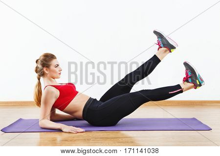 Lovely sportive girl wearing snickers, black leggings and red short top doing leg raise on purple matt at gym, fitness, white wall and wooden floor, portrait.