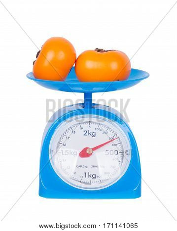 Persimmon On Kitchen Scale Isolated On White Background