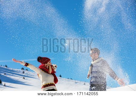 Snowball fight. Winter couple having fun playing in snow outdoors. Young joyful happy multi-racial couple