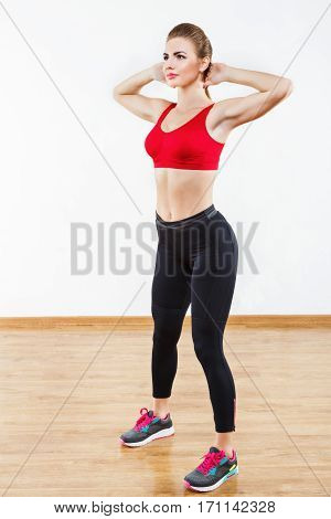 Fit sportive girl wearing snickers, black leggings and red short top standing at gym holding hands behind head, fitness, white wall at background, copy space.