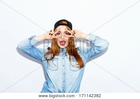 Attractive teenage red-haired girl with long hair wearing blue shirt and cap, exited emotions, copy space, white background, pathos style, portrait.