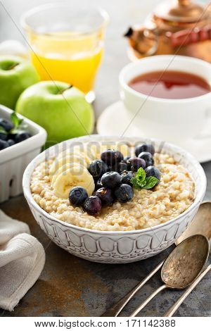 Steel cut oatmeal porridge with banana and blueberry for breakfast poster