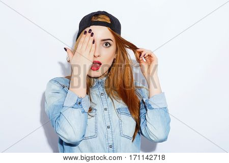 Gorgeous teenage red-haired girl with long hair wearing blue shirt and black hat, surprised, open mouth, red lips, black manicure, portrait, copy space, white background.