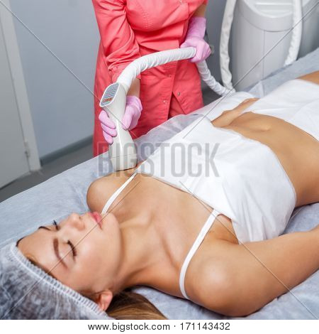 Vacuum massage the shoulder girdle of a young girl. Hardware cosmetology. Spa Studio. Rejuvenation and skin tightening.